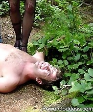 Domme trampling a male slave in the forrest